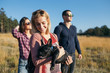 Small group of teenagers enjoying outdoors with beautiful black French bulldog. Sunny day. Autumn mountain nature.
