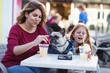 Mother and daughter enjoying with their French bulldog in cafeteria.