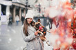 Beautiful brunette woman standing with her adorable French bulldog next to candies selling on street.