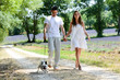 young happy man woman couple walking with dog summer vacation