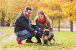 smiling couple with dog in autumn park